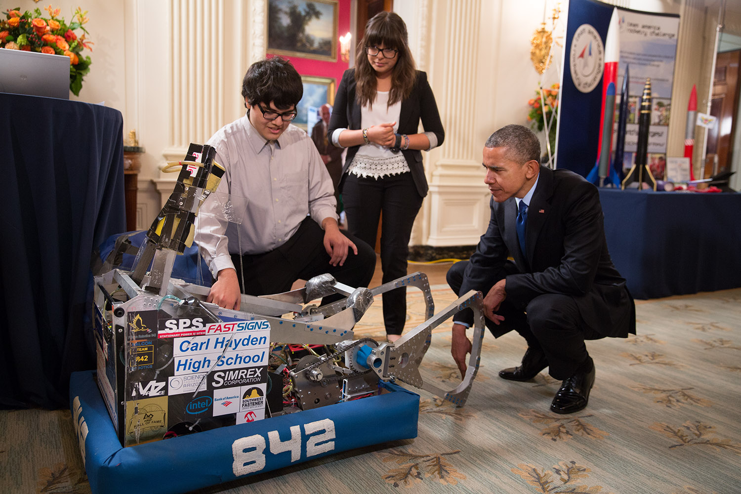 Students show President Obama their science project.